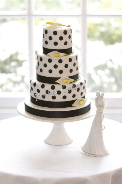 three tier black polka dot wedding cake with calla lilies